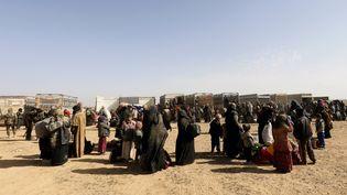 Des civils se rassemblent à un avant-poste des Forces démocratiques syriennes, près du village de Baghouz, en Syrie, près de la frontière irakienne, le 26 janvier 2019. (DELIL SOULEIMAN / AFP)