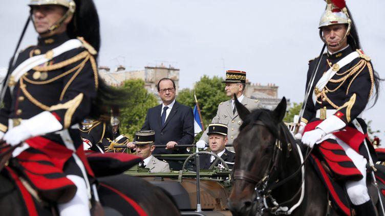 Le président François Hollande dans son véhicule militaire parade sur les Champs-Elysées, le 14 juillet 2014. (GONZALO FUENTES / AFP)