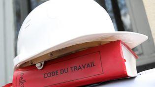 Un casque de chantier sur un code du travail. Photo d'illustration. (CHRISTOPHE BERTOLIN / MAXPPP)