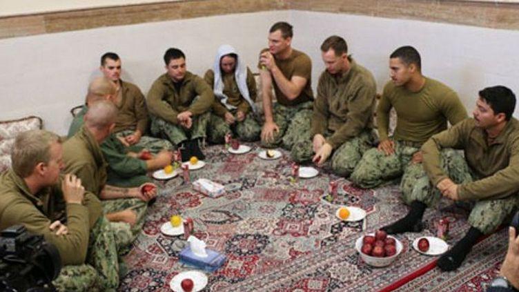 Les dix marins américains, dont une femme (la tête couverte au centre de l'image), égarés dans les eaux territoriales iraniennes, arrêtés et libérés après avoir présenté des excuses et témoigné avoir été bien traités lors de leur brève détention, le 13 janvier 2015. (AFP PHOTO / SOURCE / IRAN'S REVOLUTIONARY GUARDS WEBSITE)