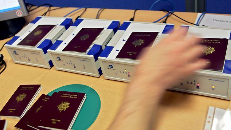 Un employé de l'Imprimerie nationale de Flers-en-Escrebieux, près de Douai (Nord), positionne des passeports pour activer les puces électroniques, le 12 avril 2006. (PHILIPPE HUGUEN / AFP)