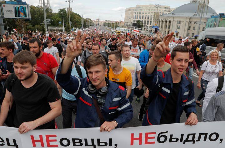 Des manifestants, parmi lesquels des ouvriers d'une fabrique de tracteurs, manifestent à Minsk le 14 août 2020. (VASILY FEDOSENKO / REUTERS)