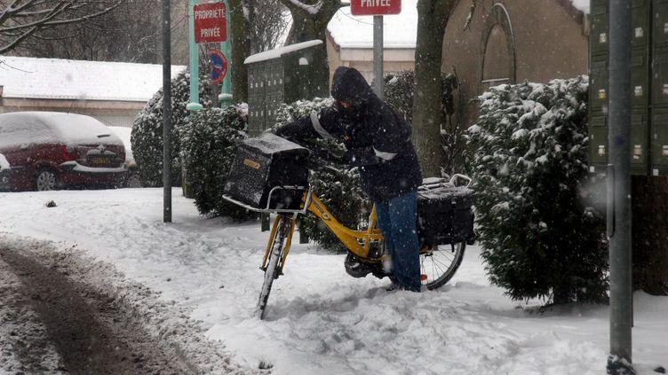 Un postier à vélo travaille sous la neige à Thionville (Lorraine), en décembre 2009. (PELAEZ JULIO / MAXPPP)