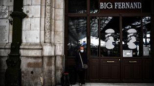 Un homme portant un masque attend un train à la Gare de Lyon, à Paris le 17 mars 2020. (CHRISTOPHE ARCHAMBAULT / AFP)