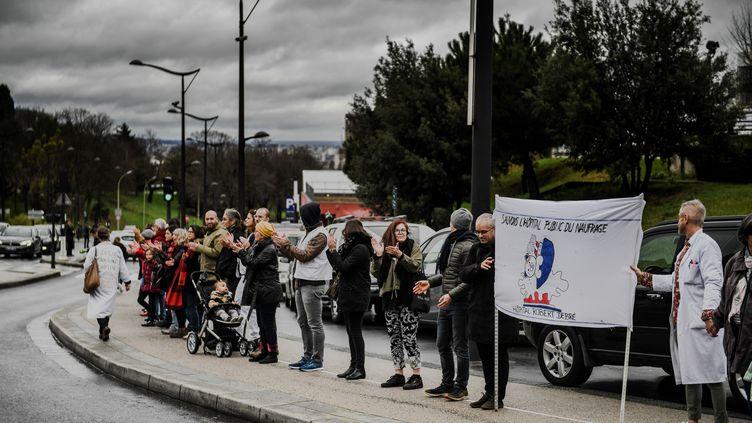 Des manifestants forment une chaîne humaine devant l'hôpital Robert-Debré, le 2 février 2020, à Paris. (MARTIN BUREAU / AFP)