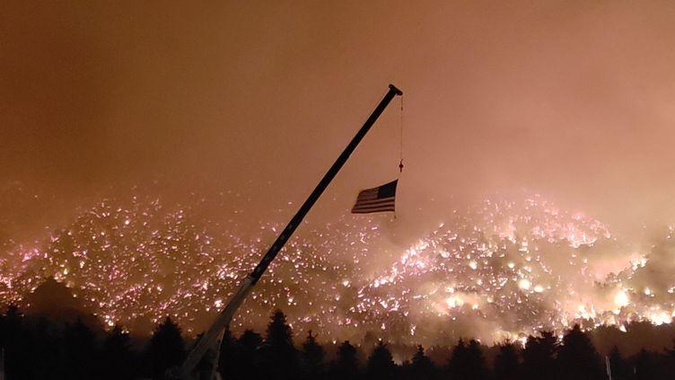 Un drapeau américain flotte devant les flammes de Lake Christine, le 4 juillet 2018, à Basalt dans le Colorado (Etats-Unis). (RONALD KIMBEL / CROWDSPARK)