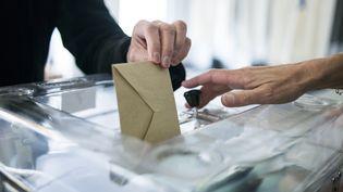 Un homme en train de voter en 2014 à Saint-Cloud. (FRED DUFOUR / AFP)