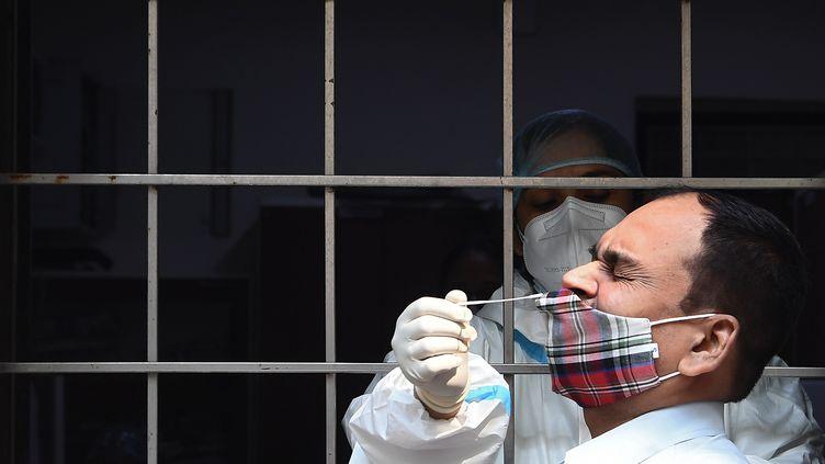 Un homme est testé pour le Covid-19 dans un centre de dépistage à New Delhi (Inde), le 19 octobre 2020. (SAJJAD HUSSAIN / AFP)