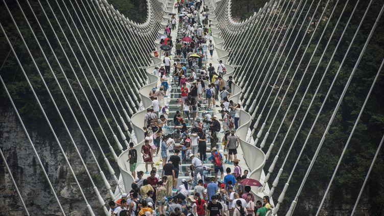 Des visiteurs sur le plus long pont en verre du monde,àZhangjiajie en Chine, le 21 août 2016. (FRED DUFOUR / AFP)