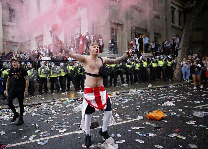 Un supporter anglais devant les forces de l'ordre, à la fanzone de Trafalgar Square, avant la finale de l'Euro, le 11 juillet. (TOLGA AKMEN / AFP)
