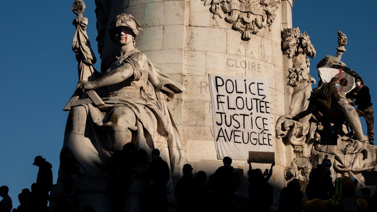 """Une banderole visible sur la statue """"Le Triomphe de la République"""", place de la République à Paris, le 28 novembre 2020, lors d'une manifestation contre le projet de loi sur la """"sécurité globale"""". (JOEL SAGET / AFP)"""