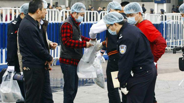 Des policiers chinois prélèvent des indices à la gare de Canton (Chine), où neuf personnes ont été blessées par un homme armé d'un couteau, le 6 mars 2015. (IMAGINECHINA / AFP)