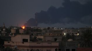 Des flammes et la fumée se dégagent, le 29 juillet au matin, de l'incendie d'une citerne de carburant à Tripoli, causé la veille par des combats entre deux milices rivales pour le contrôle de l'aéroport voisin. Mardi soir, le feu n'était toujours pas maitrisé. (SABRI ELMHEDWI / MAXPPP)