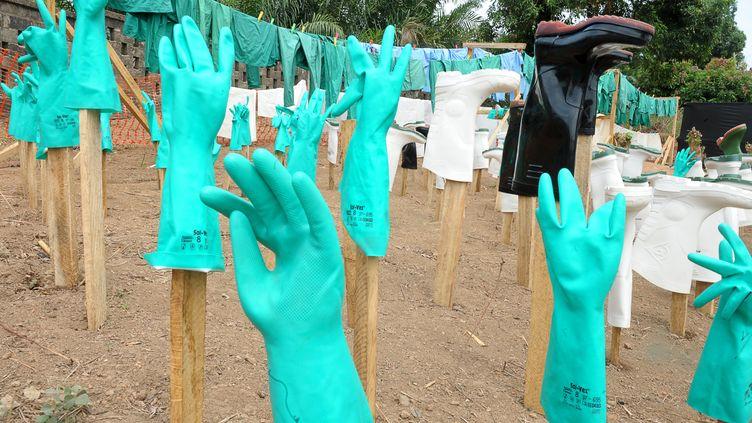 Des gants et des bottes utilisés par les médecins sèchent au soleil dans le centre pour les victimes d'Ebola, le 1er avril 2014 à Guedekou (Guinée). (SEYLLOU / AFP)