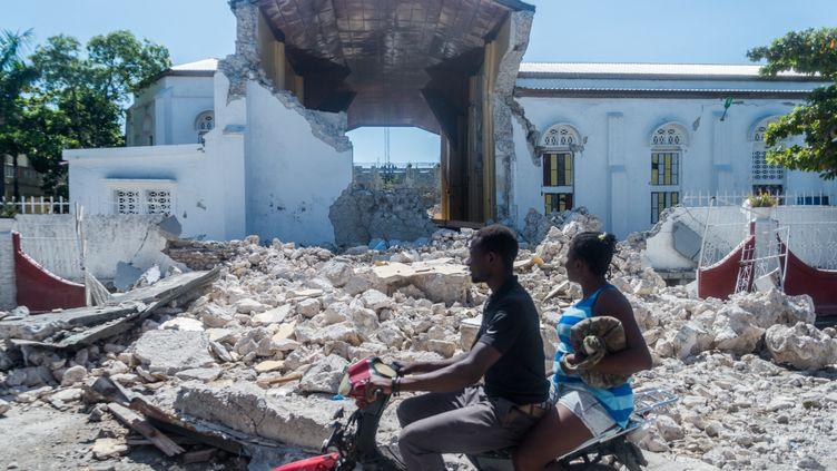 Deux personnes passent devant les ruines du Sacré coeur des Cayes dans la ville de Les Cayes en Haïti le 15 août 2021. (REGINALD LOUISSAINT JR / AFP)
