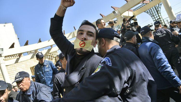 Un policier interpelle un manifestant lors d'un rassemblement de journalistes protestant contre la couverture médiatique du mouvement de contestation contre une nouvelle candidature d'Abdelaziz Bouteflika, le 28 février 2019 à Alger (Algérie). (RYAD KRAMDI / AFP)