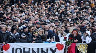 Des fans assistent à l'hommage populaire rendu en l'hommage à Johnny Hallyday, le 9 décembre 2017 à Paris. (LUDOVIC MARIN / AFP)
