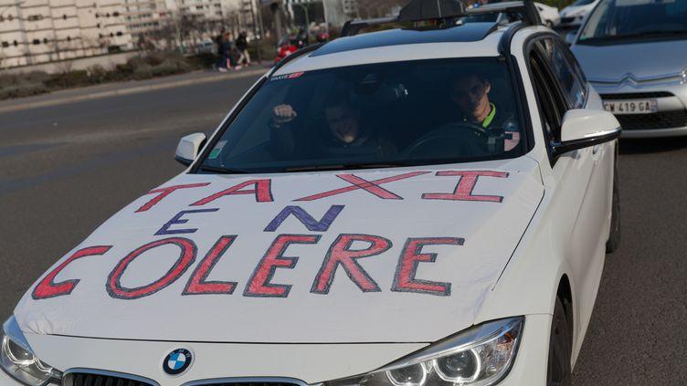 Un taxi manifeste contre les voitures avec chauffeur, à Paris, le 10 février 2014. (CITIZENSIDE / JEAN-PIERRE NGUYEN VAN HAI-BARBIER / AFP)