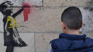 Ce pochoir d'une petite fille en gilet jaune apparue vendredi 15 février à Bordeaux est-elle l'oeuvre de Banksy ?  (Mehdi Fedouach / AFP)