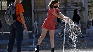 Un homme et une femme se rafraichissent à Lyon durant les fortes chaleurs, le 14 juin 2021. (ST?PHANE GUIOCHON / MAXPPP)