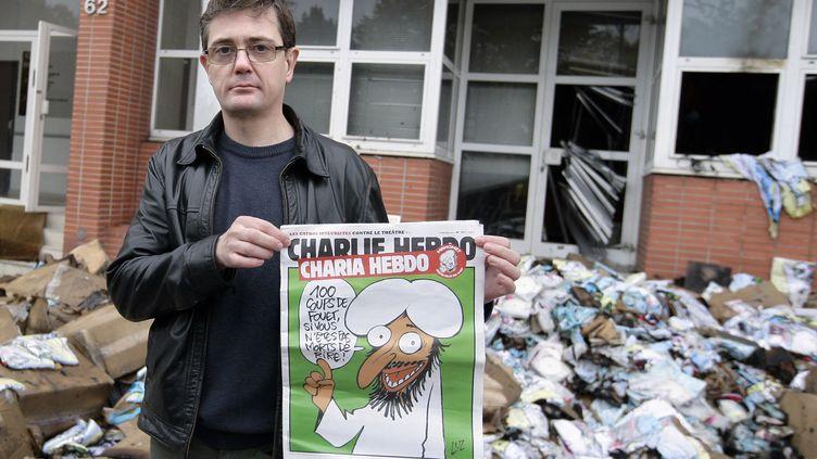 Charb, le directeur de la publication de Charlie Hebdo, montre la une de l'hebdomadaire satirique devant le siège ravagé par un incendie à Paris, le 2 novembre 2011. (ALEXANDER KLEIN / AFP)