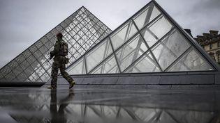 Un militaire patrouille devant la pyramide du Louvre, à Paris, le 4 février 2017. (MAXPPP)