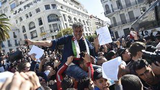 L'homme d'affaires Rachid Nekkaz, candidat déclaré à l'élection présidentielle algérienne, porté par la foule lors d'une manifestation de ses partisans à Alger, le 23 février 2019. (RYAD KRAMDI / AFP)