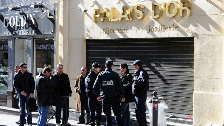 Des policiers discutent devant la bijouterie qui a été la cible d'un braquage avorté et où un passant a été blessé par balle, le 26 février 2012 dans le centre-ville de Marseille. (GERARD JULIEN / AFP)
