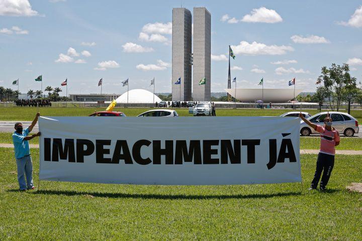 Des manifestants ont déployé une banderole pour protester contre la gestion de la pandémie par Jair Bolsonaro, le 23 janvier 2021, àBrasilia. (SERGIO LIMA / AFP)