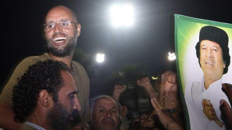 Seif al-Islam Kadhafi, fils de l'ancien «Guide» libyen Mouammar, entouré de ses partisans et de journalistes au complexe résidentiel de son père, le 23 août 2011, à Tripoli. (IMED LAMLOUM / AFP POOL / AFP)