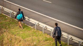 Deux migrants marchent le long de l'autoroute A25 le 14 février 2017, à hauteur deSteenvoorde (Nord). (PHILIPPE HUGUEN / AFP)
