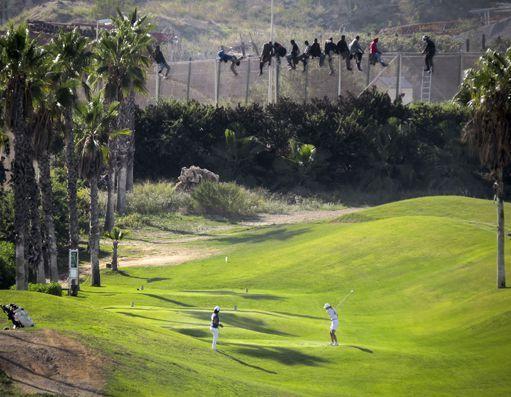 Golfeurs à Melilla jouant près de la frontière avec le Maroc, le 22 octobre 2014. A quelques mètres de la barrière où sont juchés des migrants qui tentent de passer dans l'enclave espagnole. Pour de là gagner l'Europe, en vertu des accords de Schengen. (REUTERS/Jose Palazon)