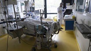 Un infirmier s'occupe d'un patient malade du Covid-19 au service de soins intensifs de l'Institut Mutualiste Montsouris, à Paris, le 21 avril 2021. (THOMAS SAMSON / AFP)