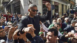 Des manifestants portent le journaliste algérien Khaled Drareni aprèsavoir été détenu par des forces de sécurité, le 6 mars 2020 à Alger (Algérie). (RYAD KRAMDI / AFP)