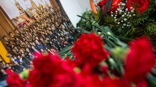 Des fleurs sont déposées devant une photo en hommage aux membres des Choeurs de l'armée rouge morts dans un crash d'avion, le 25 decémbre 2016, à Moscou (Russie). (ALEXANDER UTKIN / AFP)