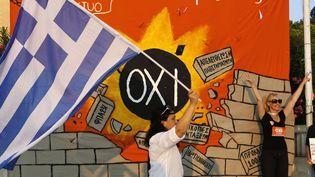"""Une femme brandit un drapeau grec devant le slogan du """"non"""" au référendum, """"oxi"""", à Athènes (Grèce), le 10 juillet 2013. (PETROS KARADJIAS/AP/SIPA / AP)"""