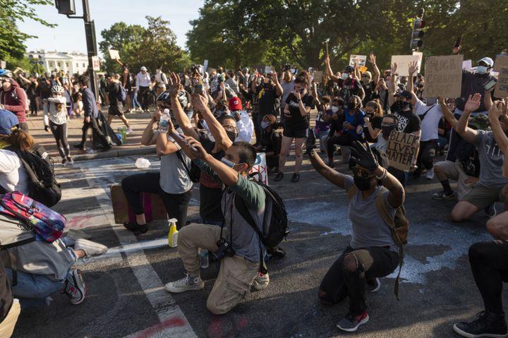 Des manifestants posent un genou à terre, lors d'unemarcheaprès la mort de George Floyd, près de la Maison Blanche, à Washington DC, le 1er juin 2020. (ROBERTO SCHMIDT / AFP)