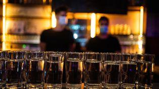 Deux barmans avec des masques sanitaires derriere le bar du Divan du monde à Paris le 8 juillet 2021. (XOSE BOUZAS / HANS LUCAS)