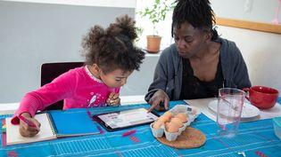 Une mère confinée avec sa fille lui apprend une recette de cuisine, le 25 mars 2020 àGrézieu-la-Varenne (Rhône). (SEBASTIEN RIEUSSEC / HANS LUCAS / AFP)