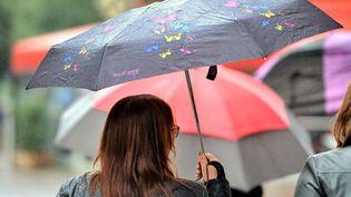 Une piétonne se protège de la pluie, dans une rue de Lille (Nord). (PHILIPPE HUGUEN / AFP)