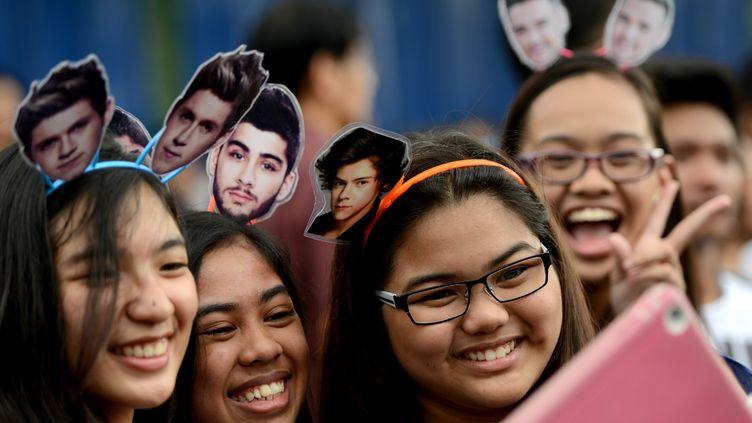 Des fans de One Direction portent des portraits de leurs idoles sur des serre-tête (Zayn est le 3e en partant de la gauche), avant un concert à Manille (Philippines),le 21 mars 2015. (NOEL CELIS / AFP)