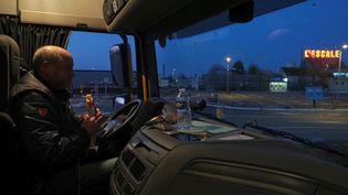 Un chauffeur routier mange dans sa cabine sur le parking durelais routier L'Escale, fermé pendant le confinement, le 26 mars 2020 à Deols (Indre). (GUILLAUME SOUVANT / AFP)