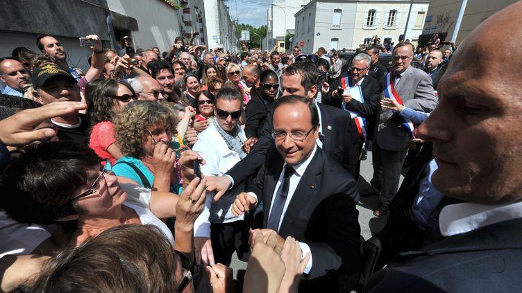 Le président François Hollande salue des habitants de La Roche-sur-Yon (Vendée), après une visite de l'agence locale de Pôle emploi, le 6 août 2013. (FRANK PERRY / AFP)