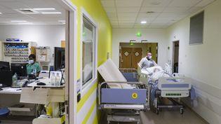 Un personnel soignantdéplaçant le lit d'un patient atteint du Covid-19 dans un hôpital. (SEBASTIEN BOZON / AFP)