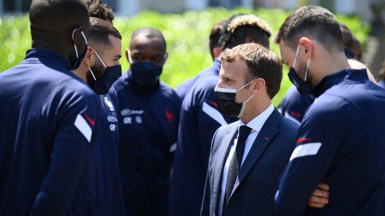 L'échange entre Emmanuel Macron et Karim Benzema lors de la visite du président de la République à Clairefontaine, jeudi 10 juin 2021. (FRANCK FIFE / AFP)