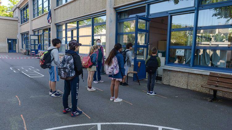 Des élèves attendent de rentrer en classe dans une école de Mantes-la-Jolie (Yvelines), le 19 mai 2020. (ISA HARSIN/SIPA)