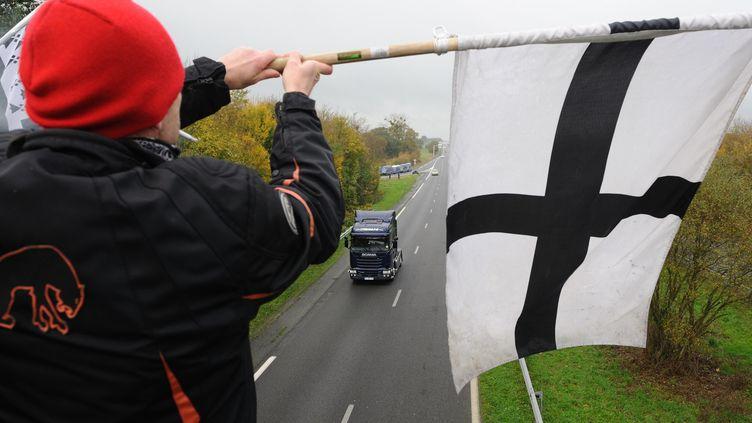 """Un """"Bonnet rouge"""" aux abords d'un portique écotaxe à Montauban-de-Bretagne, près de Rennes, le 23 novembre 2013. (SEBASTIEN SALOM-GOMIS / SIPA)"""