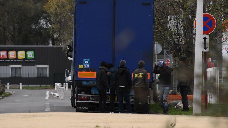 Des migrants tentent de se glisser dans un camion à Calais (Pas-de-Calais), le 14 novembre 2017. (DENIS CHARLET / AFP)
