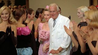 Le couturier français Hubert de Givenchy, applaudi par ses modèles après un défilé à Paris, le 11 juillet 1995. (LIONEL CIRONNEAU / AP / SIPA)