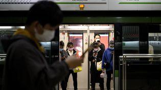 Des Chinois portant des masques dans le métro à Shanghai (Chine), le 25 février 2020. (NOEL CELIS / AFP)